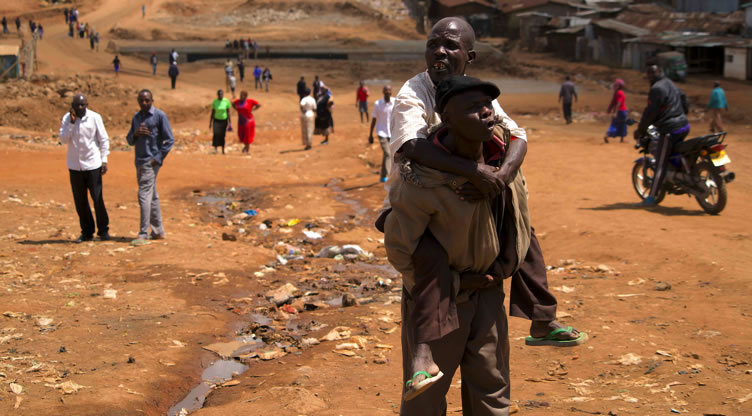 A man carries his disabled friend to a polling station in Kibra's Laini Saba.
