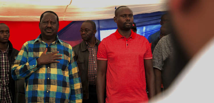 ODM leader Raila Odinga with party flag-bearer Bernard Imran Okoth (left) sings the national anthem at a rally on Kiambere Road.