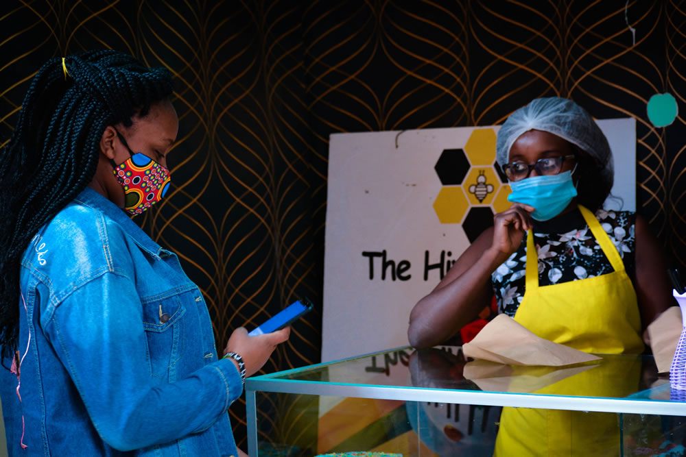 Businesses in Nairobi have to adhere to government regulations of social distancing, sanitizing and wearing of masks as they carry out their operations. At Hive pastries in Thika town, a customer in a facemask waits in line as she was purchasing pastry.
