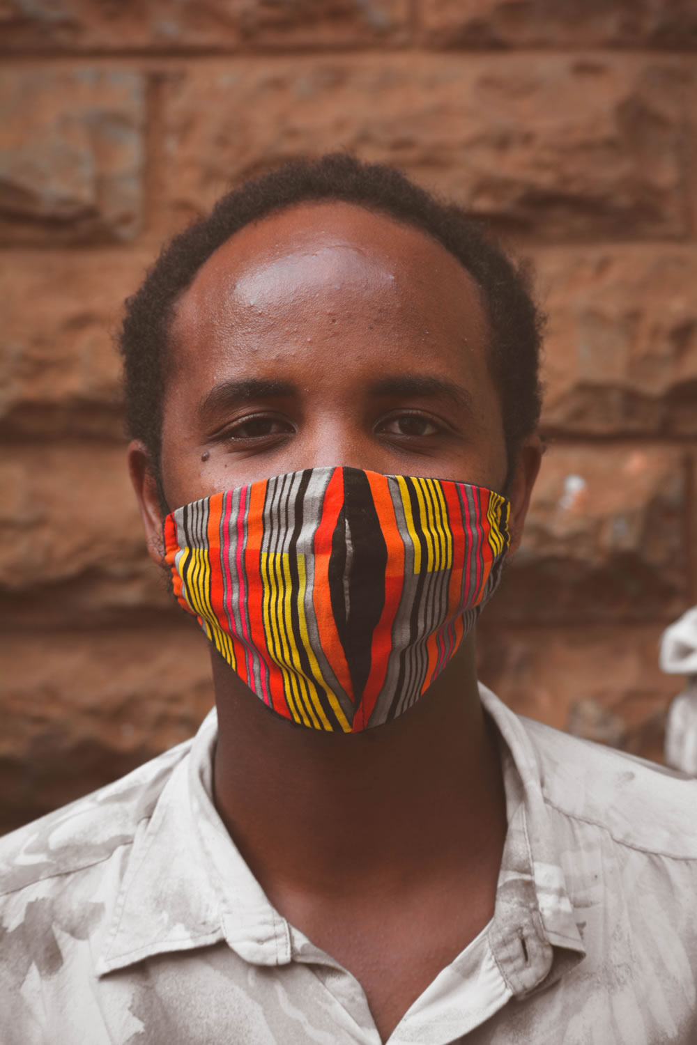 Caleb Kamau, a mask seller poses for a picture donned in a facemask