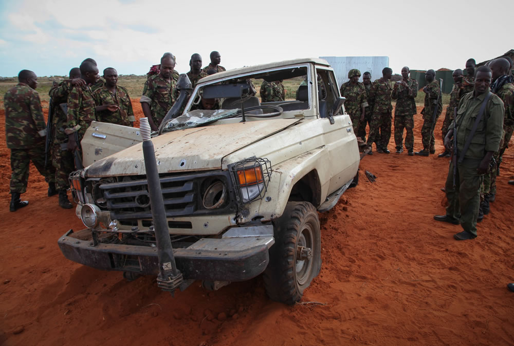 Kenyan soldiers serving with the African Union Mission in Somalia (AMISOM) inspect a destroyed vehicle belonging to Al Qaeda-affliated extremist group Al Shabaab at Kismayo Airport in southern Somalia, 22 August, 2013. AU-UN IST Photo / Ramadaan Mohamed.