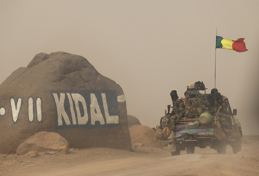 Malian soldiers traveling in convoy across the desert arrive at the entrance to Kidal in northern Mali. Credit: AP Photo/Rebecca Blackwell